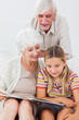 Smiling girl reading with grandparents