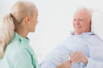Home nurse giving man glass of water