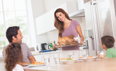 Mother bringing roast turkey to table