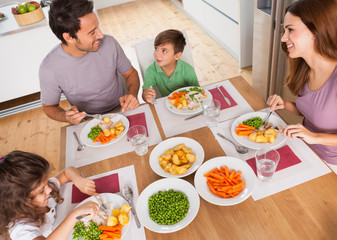 Family smiling around a healthy meal