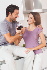 Couple toasting with arms crossed with a glass of wine