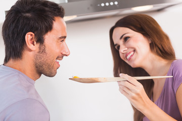 Man tasting dish on wooden spoon