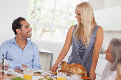 Happy wife bringing turkey to the table