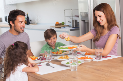 Mother serving vegetables to daughter at dinner
