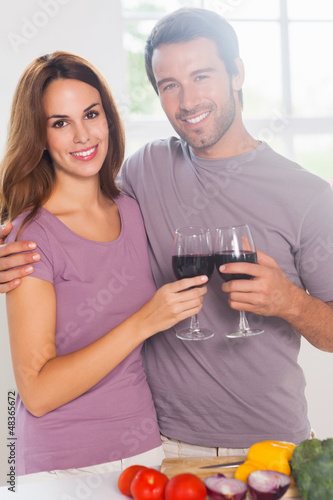 Lovers toasting with a glass of wine and looking camera
