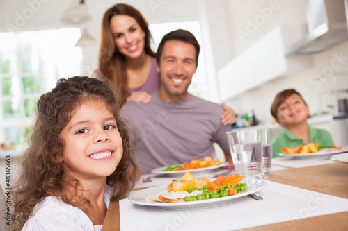 Family smiling at the camera at dinner table