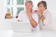 Old couple surprised in front of a laptop
