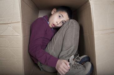 Worried teenage boy sitting in cardboard box
