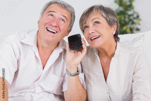 Old couple listening to a smartphone