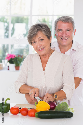 Portrait of a woman cutting vegetables with her â€&#