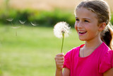Allergy season - lovely girl blowing dandelion