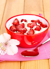 Cottage cheese in red bowl with sliced strawberries