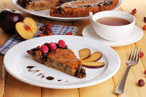 Tasty pie on plate on wooden table