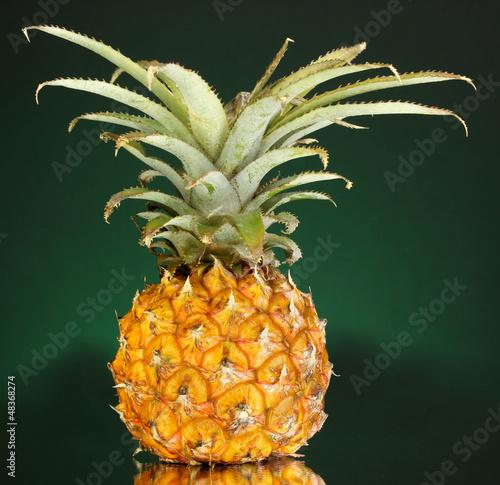 Ripe pineapple on dark green background