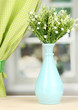 Decorative flowers in vase on windowsill