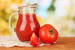 Full jug of tomato juice, on wooden table on bright background