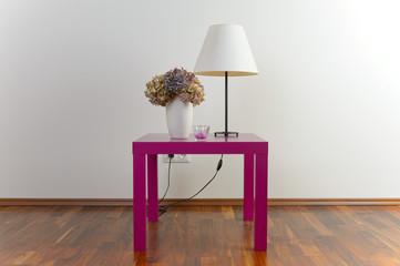 Violetter Tisch mit weißer Stehlampe und Blumenvase - Deko