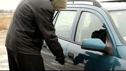 Robber with a crowbar near car