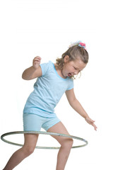 Adorable blond girl having fun in the studio with a hula hoop