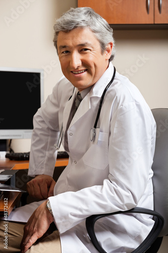 Male Doctor Sitting On Chair At Clinic