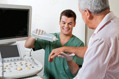 Technician Putting Gel On Patient's Hand