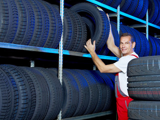 Car mechanic looking for a tire in a tire store