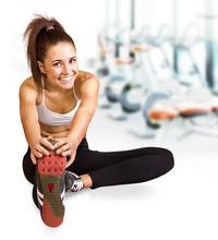 Schöne junge Brünette, die Dehnung der Muskeln im Fitness-Studio