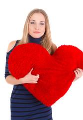 Young beautiful girl hugs a big soft heart