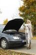 Frau kontrolliert Ölstand beim Auto