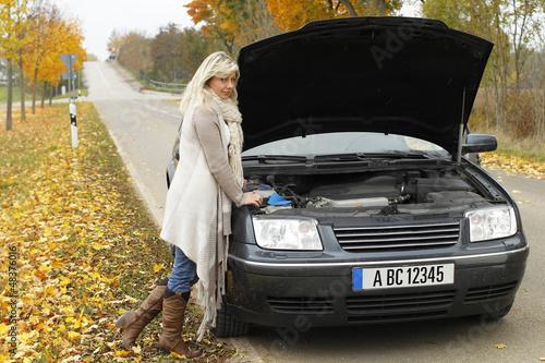 Frau steht ratlos an der Motorhaube bei Panne