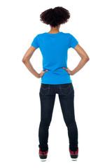 Back pose of young woman facing wall