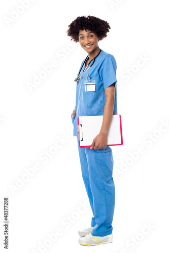 Medical expert posing sideways, holding clipboard