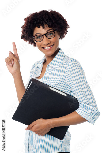 Young secretary holding file and pointing upwards