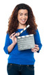 Cute woman in blue attire holding clapperboard