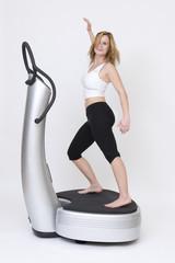 Junge sportliche Frau tanzt Zumba auf einer Powerplate