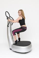 Eine junge sportliche Frau trainiert stehend auf Powerplate