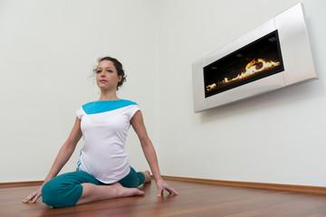 Eine junge Frau zeigt sitzend eine Yoga Figur zur Entspannung