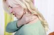 Hübsche blonde Frau mit Nackenschmerzen