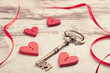red wooden hearts on wooden board with key and ribbon