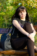 Casual young woman sitting on a bench