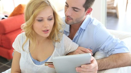 Cheerful young couple doing online shopping with tablet