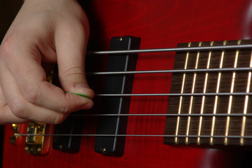 Playing on bass guitar with red body
