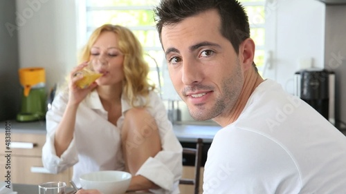 Young couple having breakfast in home kitchen