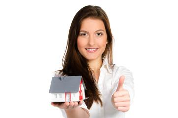 brünette frau zeigt modellhaus und daumen hoch
