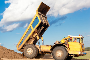 Heavy dump truck unloading soil on the sand