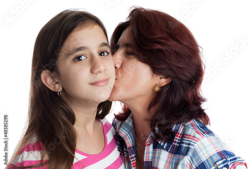 Hispanic mother kissing her beautiful daughter