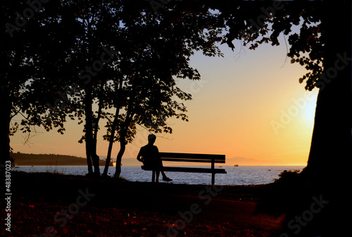 Man Sitting On Bench By A Beach During A Beautiful Sunset