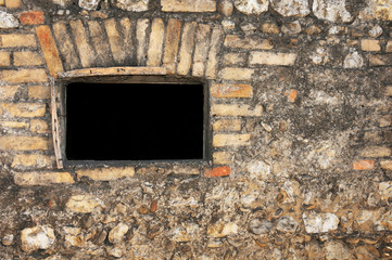window without glass in an ancient brick wall