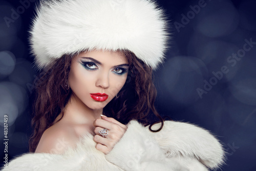 Winter woman in fur coat. Glamour portrait of beautiful woman mo