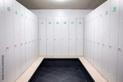Gym dressing room with lots of white lockers with green numbers